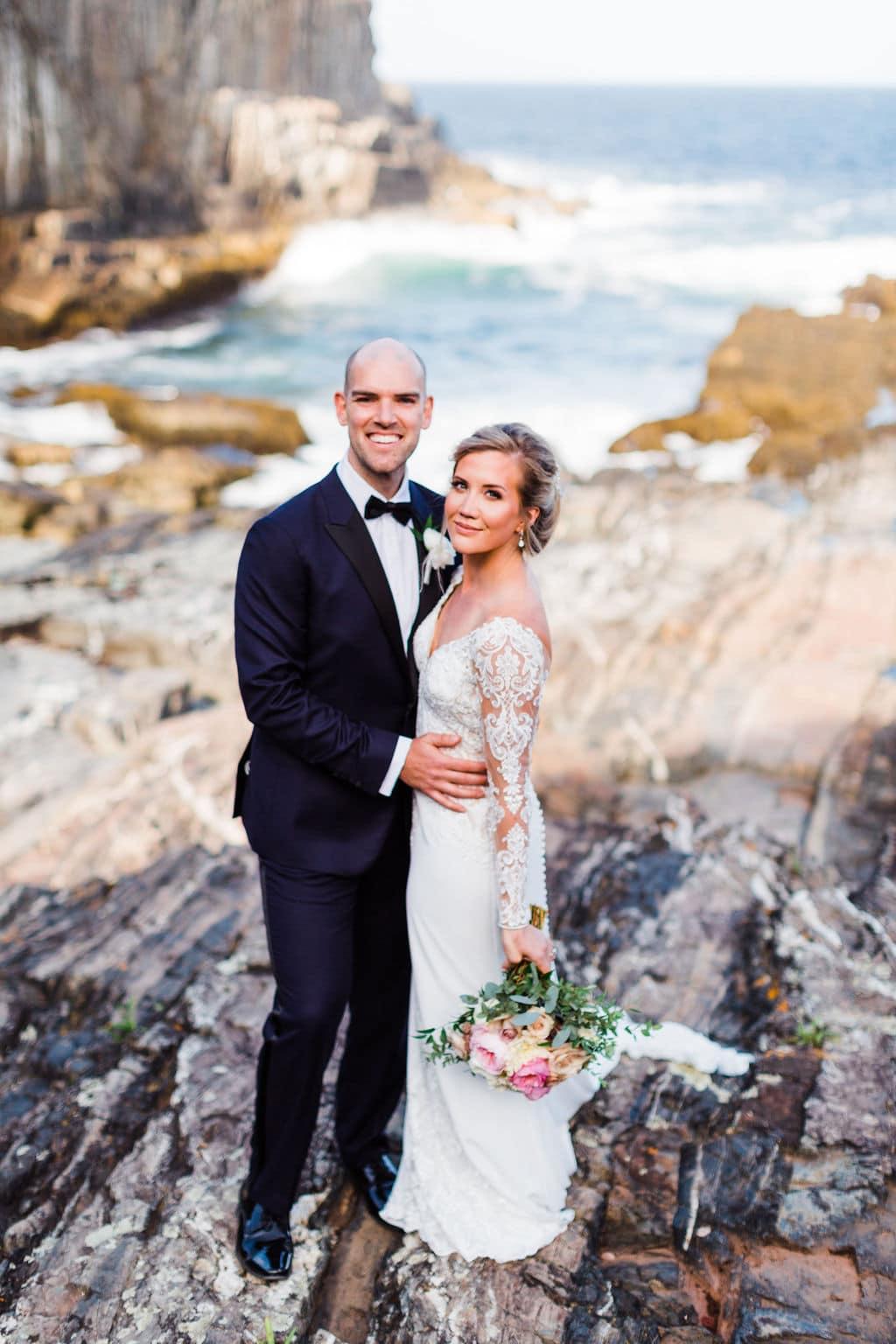 Wedding couple on the rocks after their coastal Maine wedding